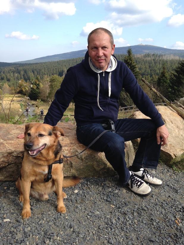 Mann und Hund in Torfhaus, im Hintergrund der Brocken