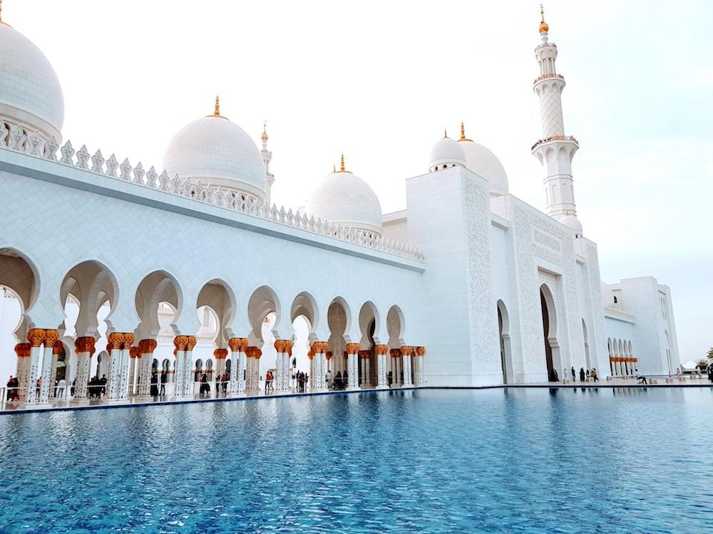Die schneeweiße Moschee ist von blauem Wasser umgeben